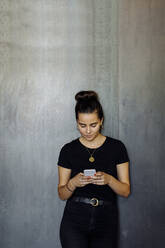 Portrait of casual young businesswoman using smartphone in front of a grey wall - SODF00381