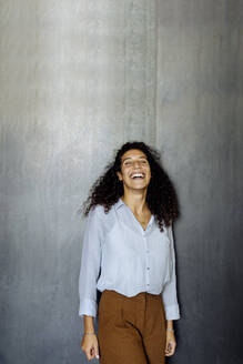 Portrait of a laughing young businesswoman standing in front of a grey wall - SODF00387
