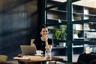 Happy casual young businesswoman with laptop in loft office - SODF00390