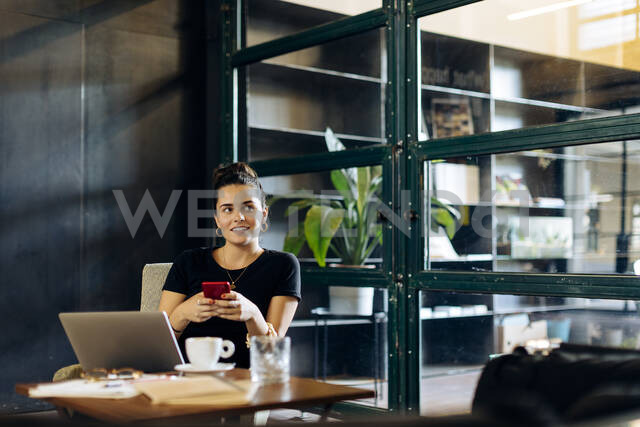 Casual young businesswoman with laptop and smartphone in loft office - SODF00393 - Sofie Delauw/Westend61