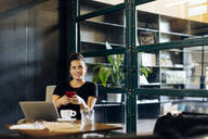Casual young businesswoman with laptop and smartphone in loft office - SODF00393