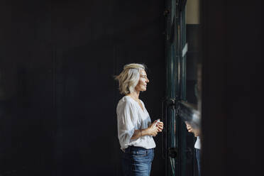Casual mature businesswoman looking out of window in loft office - SODF00396