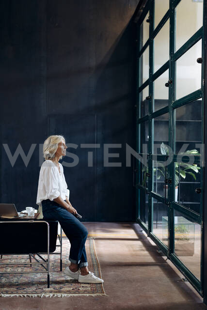 Casual mature businesswoman looking out of window in loft office - SODF00402 - Sofie Delauw/Westend61