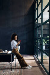Young businesswoman using smartphone in loft office - SODF00405