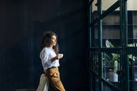 Young businesswoman looking out of window in loft office - SODF00408