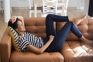 Relaxed young woman lying on couch at home - GIOF07780