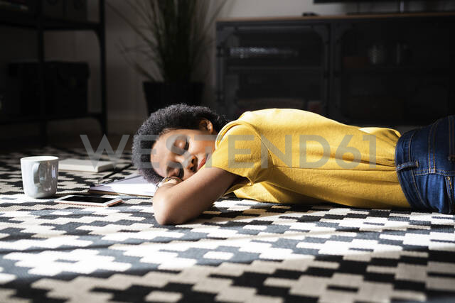 Young woman lying on the floor at home with closed eyes - GIOF07783 - Giorgio Fochesato/Westend61