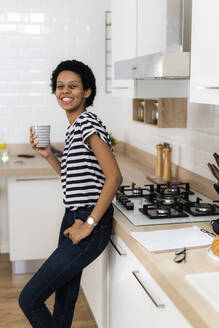 Portrait of smiling young woman holding mug in kitchen at home - GIOF07810