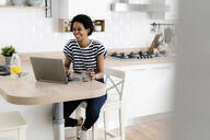 Happy young woman using laptop at home - GIOF07813
