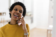 Happy young woman on the phone at home - GIOF07819