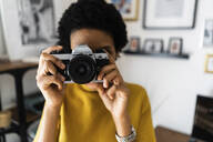 Young woman taking picture with vintage camera at home - GIOF07831