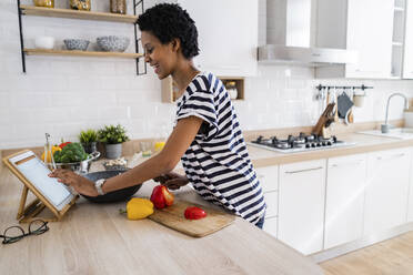 Young woman using tablet cooking in kitchen at home - GIOF07840