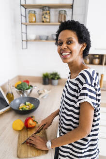 Portrait of smiling young woman cooking in kitchen at home cutting vegetables - GIOF07843