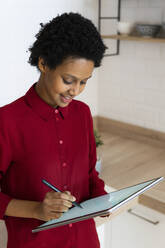 Young woman using graphics tablet at home - GIOF07849