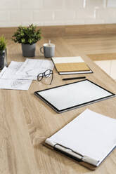 Clipboard, tablet and plan on wooden kitchen counter - GIOF07852