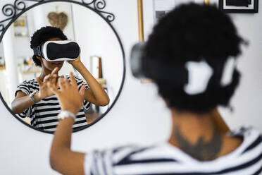 Young woman with VR glasses in front of a mirror at home - GIOF07858
