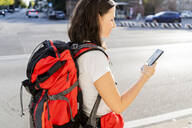 Young female backpacker with red backpack using smartphone in the city, Verona, Italy - GIOF07869