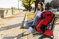 Young female backpacker with red backpack using smartphone, sitting on a benach in Verona, Italy - GIOF07875