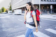 Young female backpacker using smartphone in the city, Verona, Italy - GIOF07878