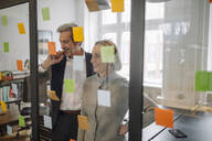 Happy colleagues looking at sticky notes at glass pane in office - GUSF02682
