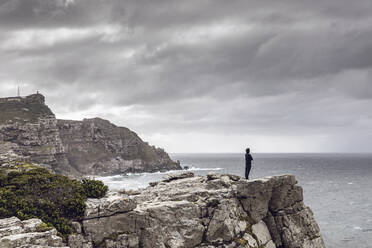 Man standing on rocky cliff looking at horizon, Cape Point, Western Cape, South Africa - MCF00327