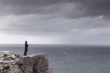 Man standing on rocky cliff looking at horizon, Cape Point, Western Cape, South Africa - MCF00330