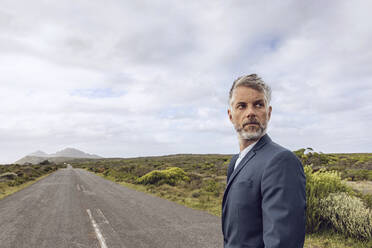 Portrait of businessman standing on country road, Cape Point, Western Cape, South Africa - MCF00333