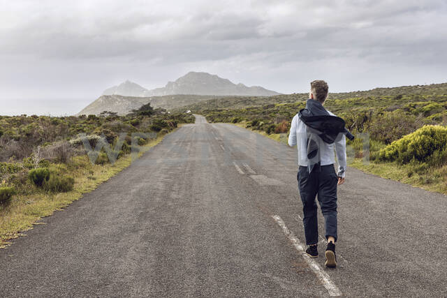 Back view of businessman walking on country road, Cape Point, Western Cape, South Africa - MCF00336 - Maya Claussen/Westend61