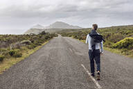 Back view of businessman walking on country road, Cape Point, Western Cape, South Africa - MCF00336
