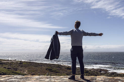Back view of businessman standing in front of the sea, Cape Point, Western Cape, South Africa - MCF00339