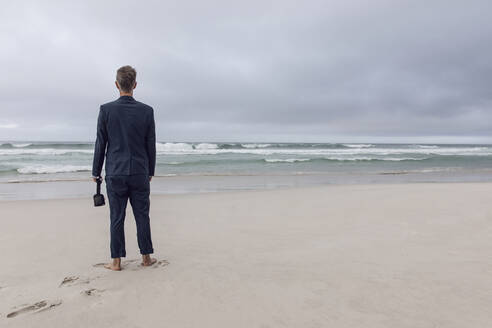 Back view of businessman standing on beach with VR glasses, Nordhoek, Western Cape, South Africa - MCF00342