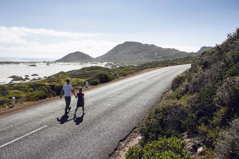 Man walking hand in hand with his daughter on country road, Cape Town, Western Cape, South Africa - MCF00345