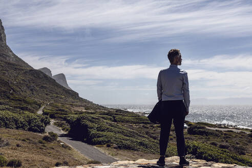 Back view of businessman standing on plateau looking to the sea, Cape Point, Western Cape, South Africa - MCF00348