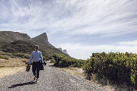 Businessman walking barefoot on country road, Cape Point, Western Cape, South Africa - MCF00351