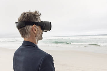 Businessman using VR glasses on the beach, Nordhoek, Western Cape, South Africa - MCF00354