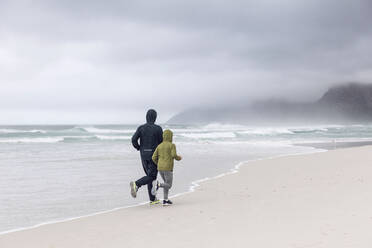 Backview of father and daughter jogging on the beach, Nordhoek, Western Cape, South Africa - MCF00357