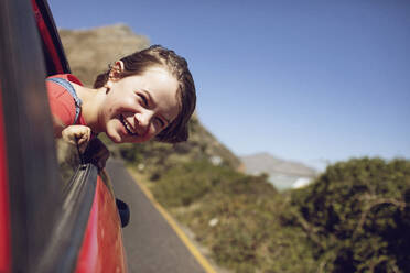 Portrait of laughing girl looking out of car window, Cape Town, Western Cape, South Africa - MCF00360