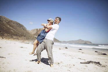 Father and daughter having fun together on the beach, Cape Town, Western Cape, South Africa - MCF00369