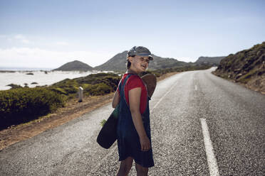 Portrait of smiling girl with skateboard standing on country road, Cape Town, Western Cape, South Africa - MCF00375