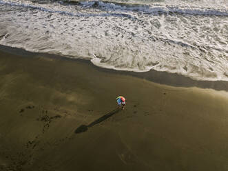 Aerial view of couple unde rainbow colors umbrella at the beach, Kedungu beach, Bali, Indonesia - KNTF03728