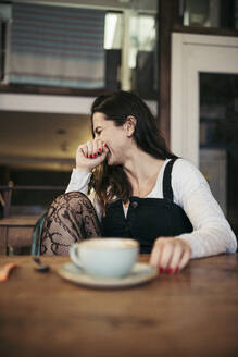 Laughing woman sitting in a coffee shop - MTBF00210