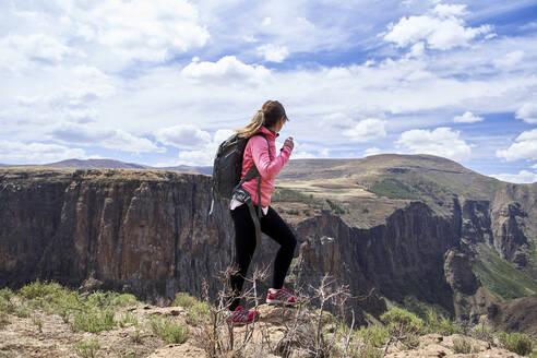 Woman hiking through the mountains, Maletsunyane Falls, Lesotho - VEGF00839