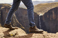 Low section of a man walking through the mountains, Maletsunyane Falls, Lesotho - VEGF00842