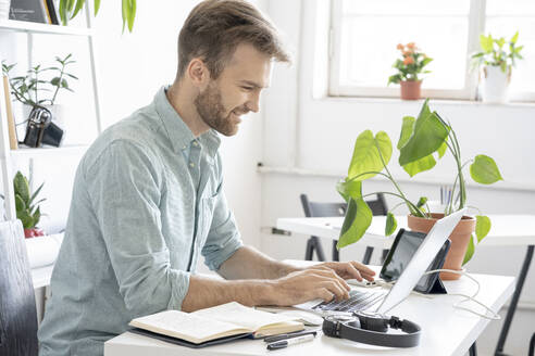 Smiling man using laptop at desk in office - VPIF01754