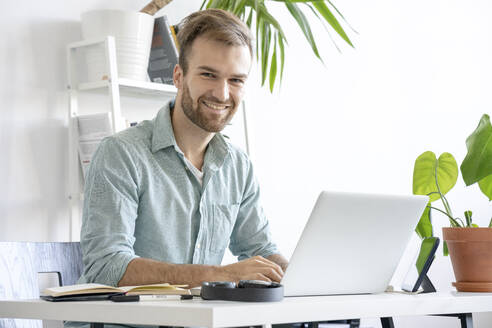 Portrait of smiling man using laptop at desk in office - VPIF01757