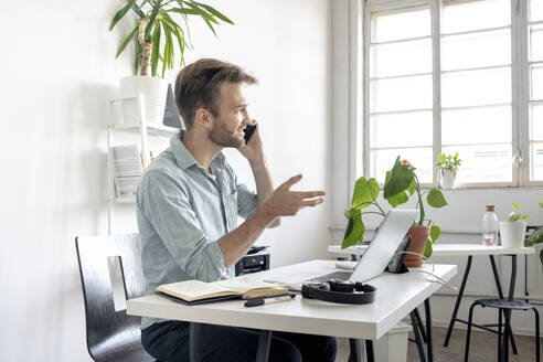 Smiling man on the phone at desk in office - VPIF01760