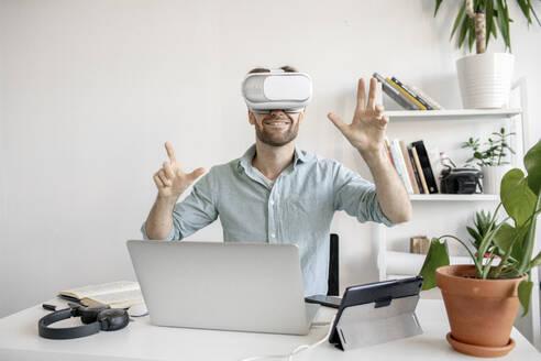 Man wearing VR glasses at desk in office - VPIF01769