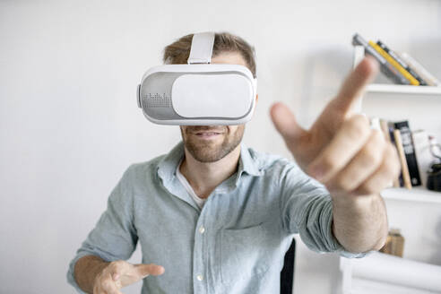 Portrait of man wearing VR glasses in office - VPIF01772