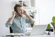 Excited man listening to music at desk in office - VPIF01775