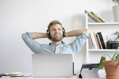 Smiling man listening to music at desk in office - VPIF01778